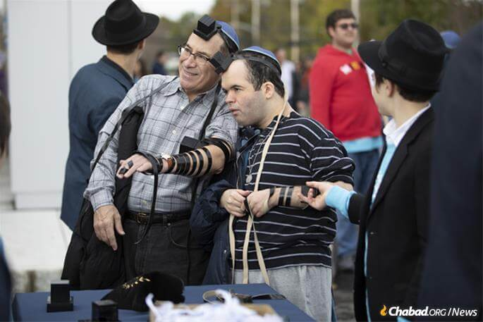 """Every soul has a unique personal mission to fulfill in this world,"" says Rabbi Zalman Grossbaum. Above, Keith Lerner puts on tefillin with his son, Max. (Photo: Mendel Grossbaum)"