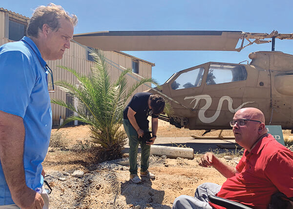 Access Israel Founder Yuval Wagner being interviewed in front of a Cobra helicopter