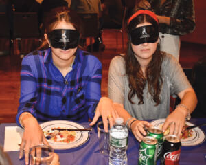 Two women try to eat blindfolded at a recent FAISR sensativity dinner at NYU