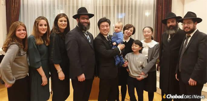 Japan's State Minister for Foreign Affairs Yasuhide Nakayama and family with Chabad of Japan emissaries at a Chanukah event last month at the Israeli embassy in Tokyo. L to R, Rachel Vaisfiche, Batya Vishedsky, Chana Sudakevich, Rabbi Shmuel Vishedsky, the Nakayamas, Rabbi Mendi Sudakevich, Rabbi Shalom Vaisfiche.