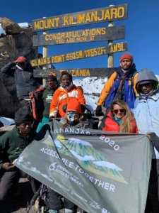 Hikers and their porters pose at the top of Mount Kilimajaro. Credit: Friends of Access Israel.