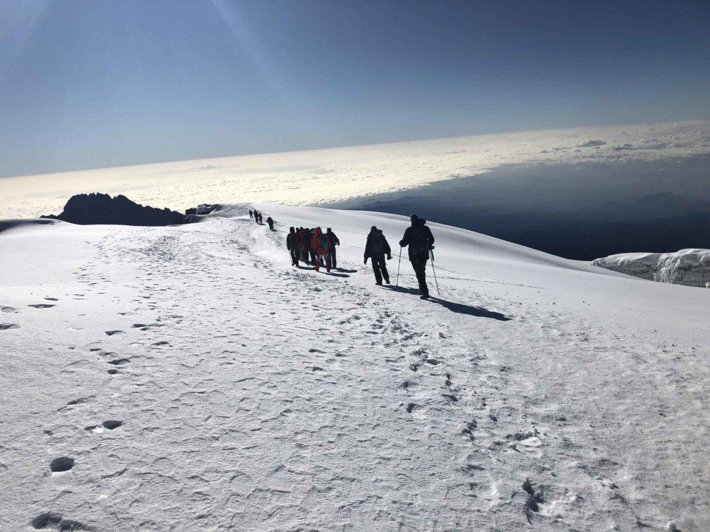 A view of the team hiking across the snow fields on the top of Kilimanjaro. Credit: Friends of Access Israel.